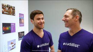 Chris and a coworker wear Cuddlist t-shirts on the set of shark tank.